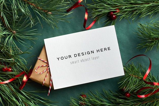 Christmas greeting card mockup with decorated gift box and pine tree branches on green