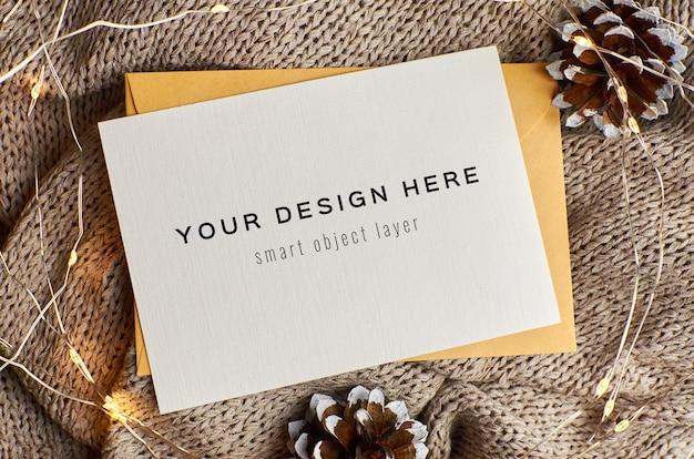 Макет рождественской открытки с украшенными шишками и огнями