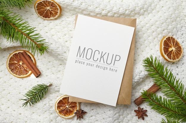 ニットの背景にドライオレンジ、スパイス、モミの木の枝とクリスマスグリーティングカードのモックアップ