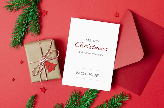 Christmas greeting card mockup with envelope and decorated gift box on red