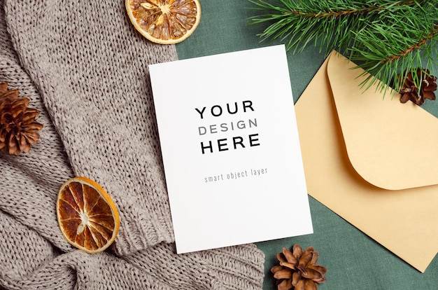 Christmas greeting card mockup with envelope, dry oranges and pine tree branches with cones