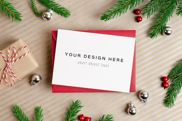 Christmas greeting card mockup with envelope, gift box and festive decorations with fir tree branches