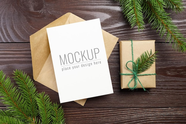 Christmas greeting card mockup with envelope, gift box and fir tree branches on dark wooden background