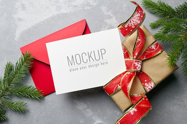 Christmas greeting card mockup with envelope, gift box and fir tree branches