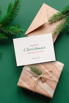 Christmas greeting card mockup with envelope, gift box and green fir tree branches