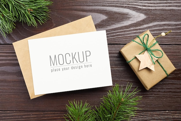 Christmas greeting card mockup with envelope, gift box and pine tree branches on dark wooden background