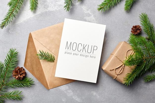 封筒、松ぼっくり、モミの木の枝とクリスマスグリーティングカードのモックアップ