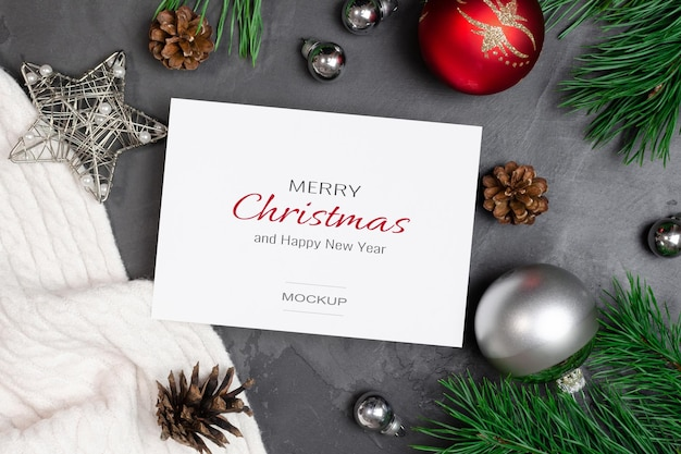 축제 장식과 콘이 있는 소나무 가지가 있는 크리스마스 인사말 카드 모형