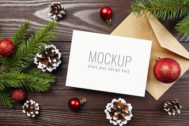 お祝いの装飾、コーン、モミの木の枝とクリスマスグリーティングカードのモックアップ