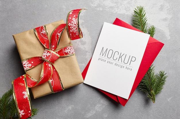 お祝いのギフトボックスとモミの木の枝とクリスマスグリーティングカードのモックアップ