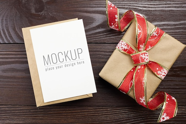 Christmas greeting card mockup with festive gift box on dark wooden background