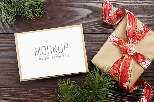 Christmas greeting card mockup with festive gift box and pine tree branches on dark wooden background