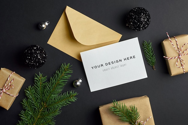 Макет рождественской открытки с еловой веткой, подарочными коробками и праздничными украшениями на темноте