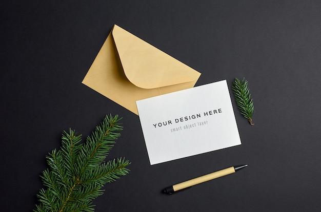 暗い紙の背景にモミの木の枝とクリスマスグリーティングカードのモックアップ
