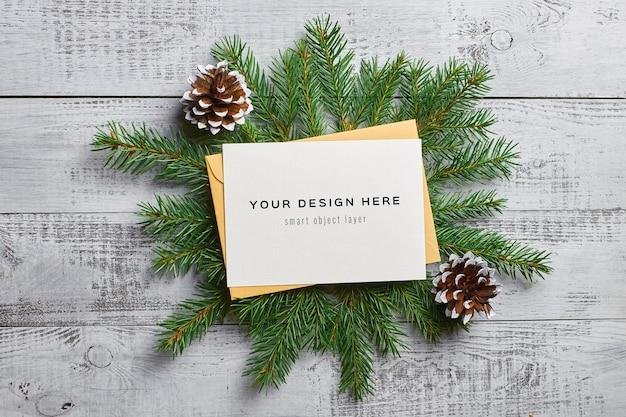 Рождественский макет поздравительной открытки с еловыми ветками и шишками