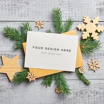 モミの木の枝と木製の装飾が施されたクリスマスグリーティングカードのモックアップ