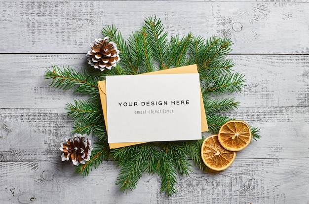 Christmas greeting card mockup with fir tree branches, dry oranges and cones