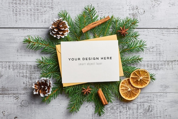 Christmas greeting card mockup with fir tree branches, dry oranges and spices