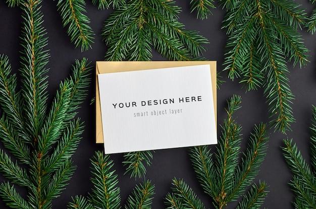 黒のモミの木の枝とクリスマスグリーティングカードのモックアップ