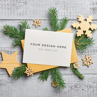 Christmas greeting card mockup with fir tree branches and wooden decorations