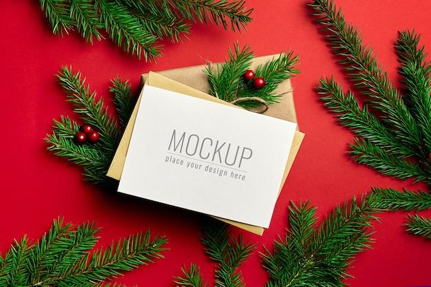 Макет рождественской открытки с подарочной коробкой и еловыми ветками на красном