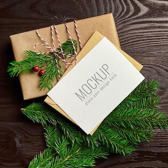 나무 배경에 선물 상자와 전나무 나무 가지와 크리스마스 인사말 카드 모형