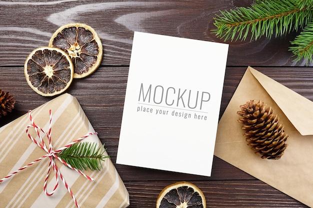 ギフトボックス、ドライオレンジ、コーン、モミの木の枝とクリスマスグリーティングカードのモックアップ