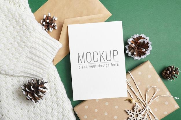 ニットの背景にギフトボックス、封筒、コーンとクリスマスグリーティングカードのモックアップ