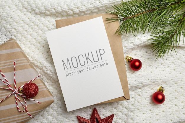 ギフトボックス、お祝いの装飾、ニットの背景に松の木の枝とクリスマスグリーティングカードのモックアップ