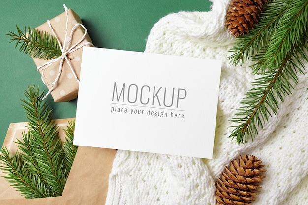 ギフトボックス、ニットの背景にコーンとモミの木の枝とクリスマスグリーティングカードのモックアップ