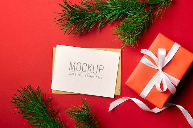 Christmas greeting card mockup with gift box and pine tree branches on red