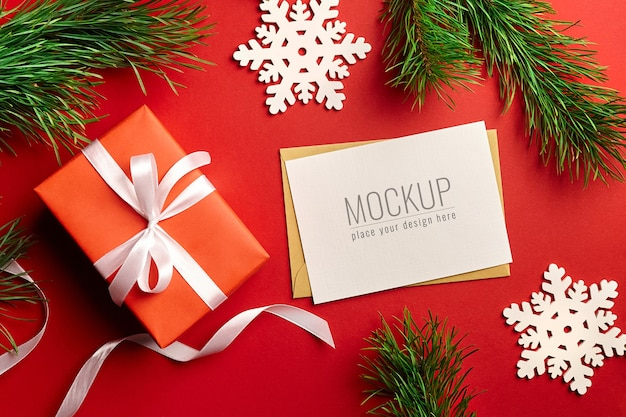 Christmas greeting card mockup with gift box, pine tree branches and wooden decorations