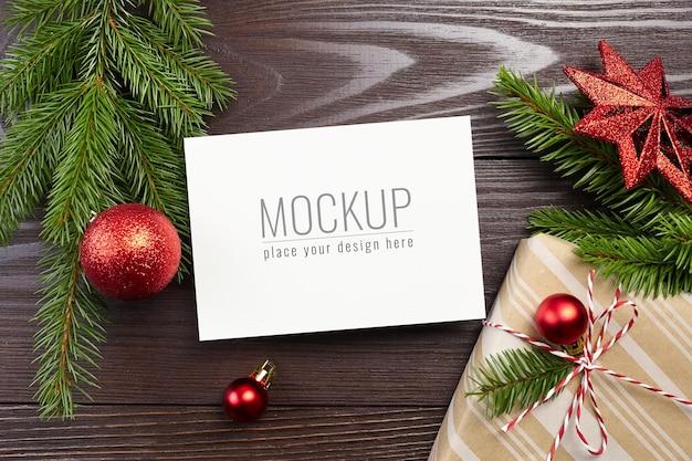 ギフトボックス、赤いお祭りの装飾とモミの木の枝とクリスマスグリーティングカードのモックアップ