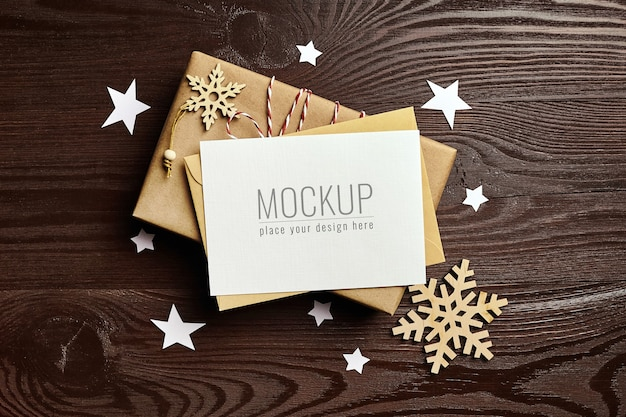 Christmas greeting card mockup with gift box and wooden decorations