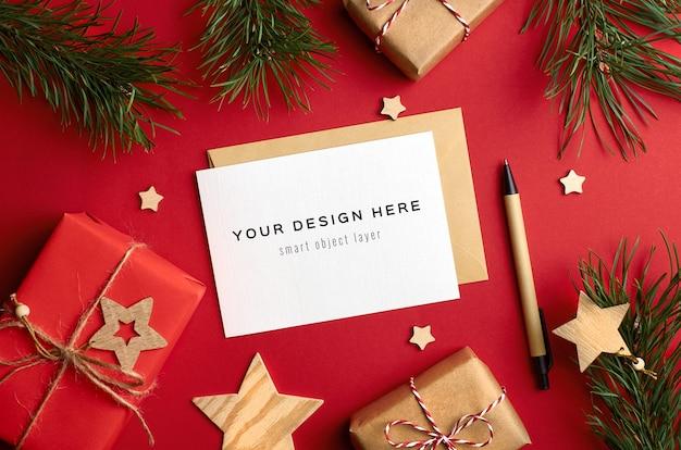 赤のギフトボックスと松の木の枝とクリスマスグリーティングカードのモックアップ