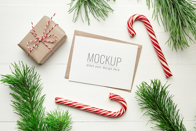 Christmas greeting card mockup with gift boxes, candy cane and pine tree branches