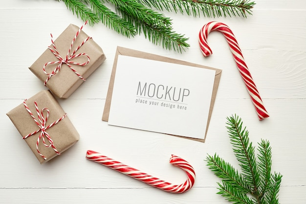 Christmas greeting card mockup with gift boxes, candy canes and fir tree branches