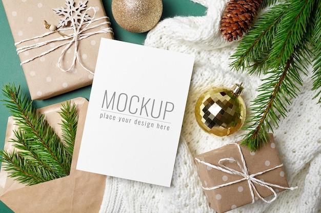 ギフトボックス、お祝いの装飾、モミの木の枝とクリスマスグリーティングカードのモックアップ