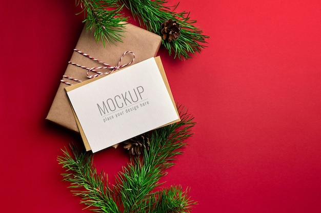 Christmas greeting card mockup with gift boxes and pine tree branches on red background
