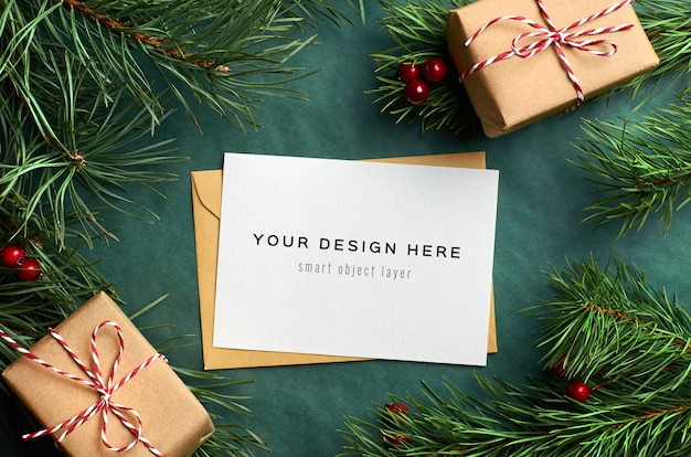 Christmas greeting card mockup with gift boxes and pine tree branches