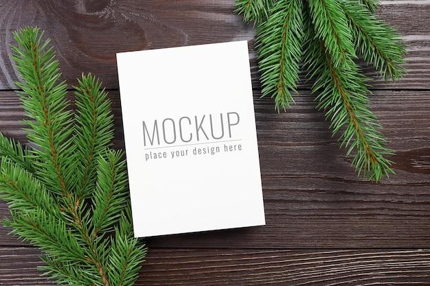暗い木製の背景に緑のモミの木の枝とクリスマスグリーティングカードのモックアップ
