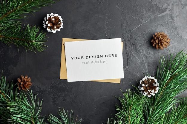 松の枝と円錐形のクリスマスグリーティングカードのモックアップ