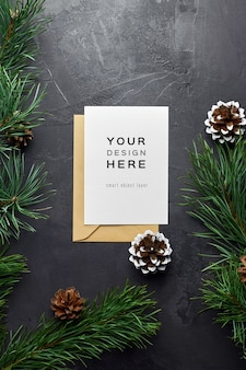 Christmas greeting card mockup with pine branches and cones on dark