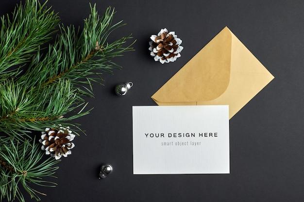 暗い松の木の枝と円錐形のクリスマスグリーティングカードのモックアップ