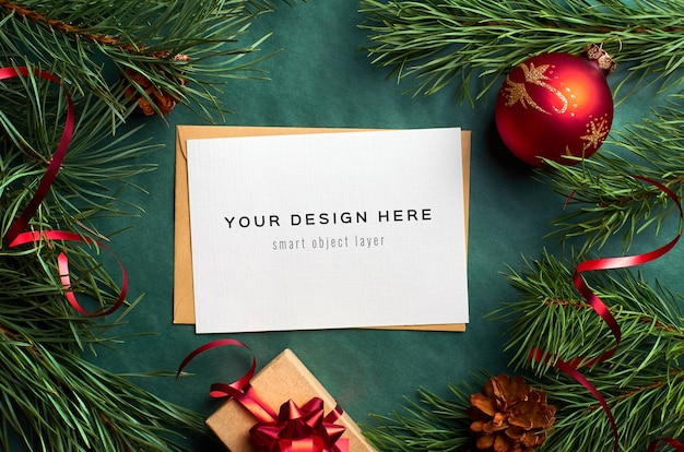 Christmas greeting card mockup with pine tree branches and festive decorations on green