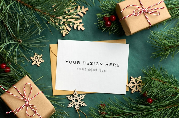 Christmas greeting card mockup with pine tree branches and gift boxes with wooden decorations on green