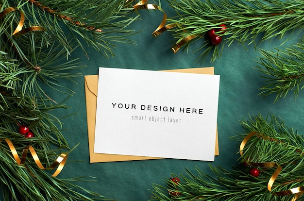 Christmas greeting card mockup with pine tree branches and gold tape decorations on green