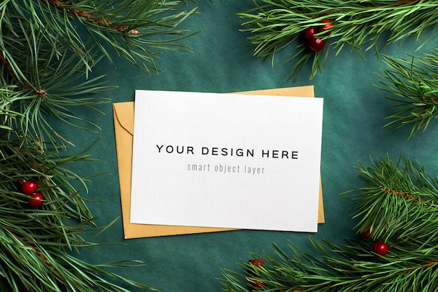 Christmas greeting card mockup with pine tree branches and holly berries on green