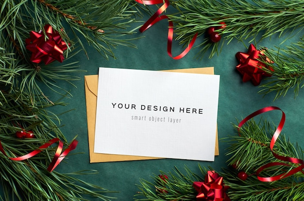 Christmas greeting card mockup with pine tree branches and red tape decorations on green
