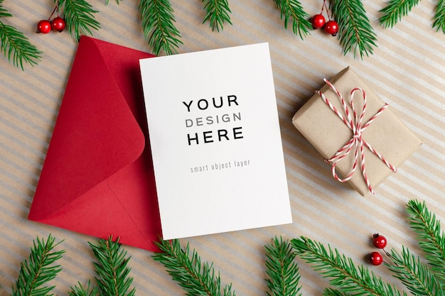 Christmas greeting card mockup with red envelope, gift box and decorated fir tree branches